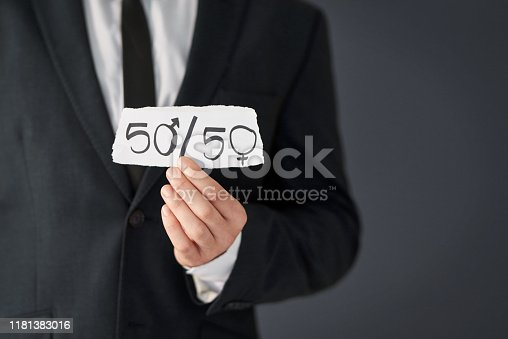 Studio shot of an unrecognizable businessman holding a piece of paper promoting gender equality against a grey background