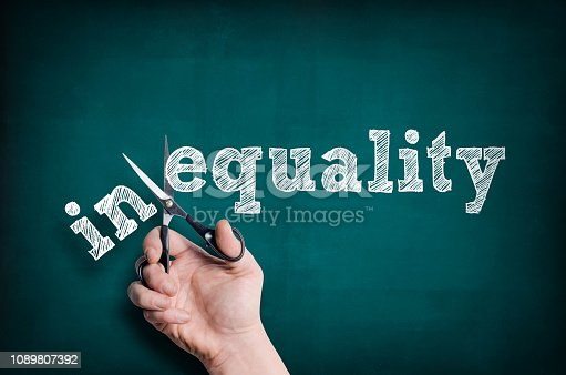 The male hand with scissors cuts word Equality from Inequality