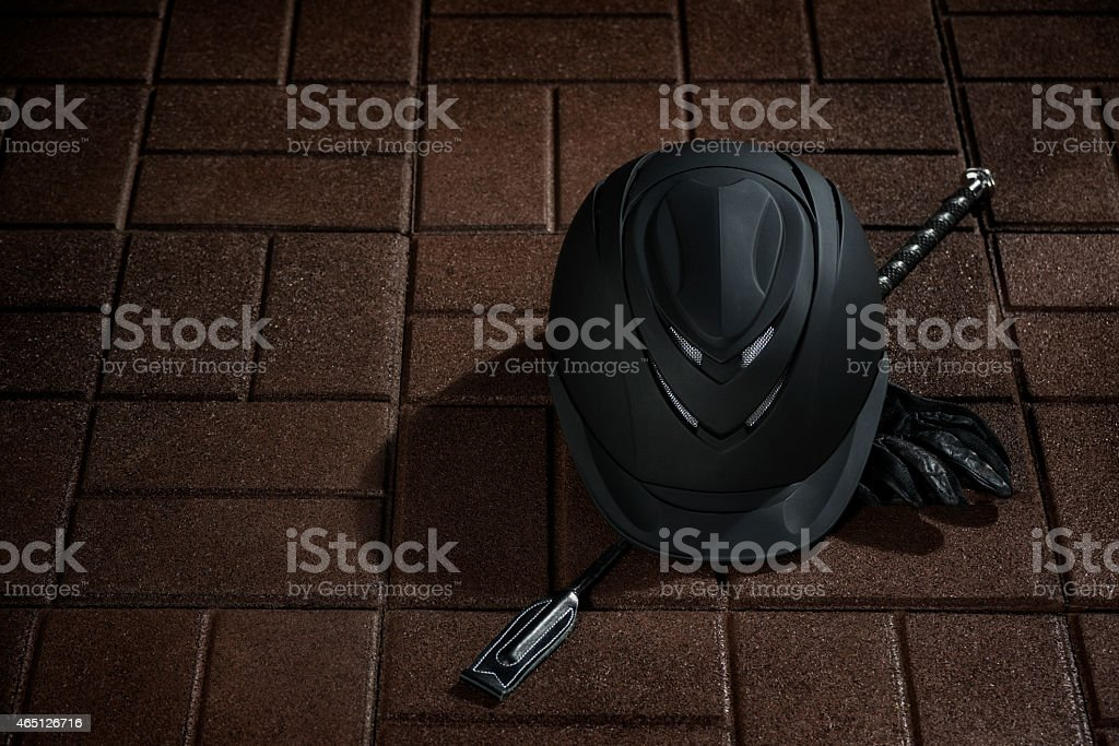 Equestrian riding helmet, crop and gloves on rubber tile floor stock photo