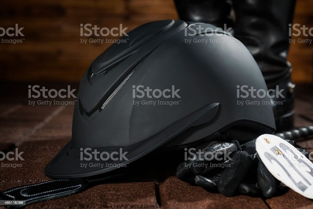 Equestrian riding helmet, crop, gloves and boots stock photo