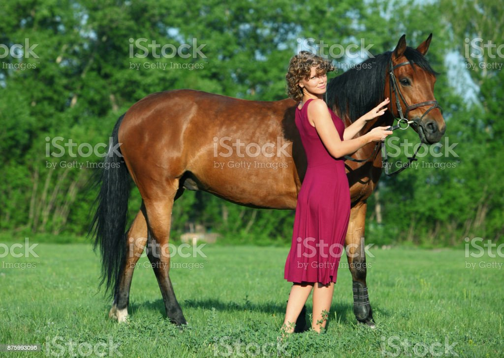 Equestrian woman in red dress horseback riding in the summer meadow stock photo