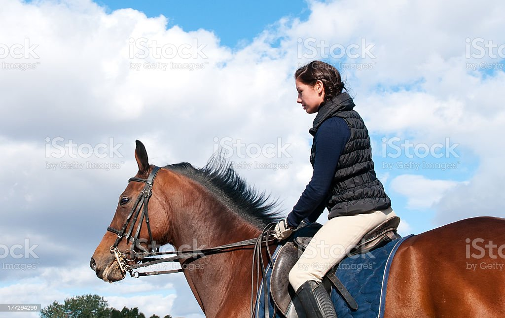 Equestrienne rides front of blue sky stock photo