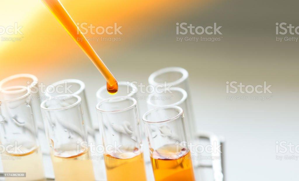 utrustning och glas för testprodukt utvinning och orange färg lösning, i kemi laboratoriet. - Royaltyfri Analysera Bildbanksbilder