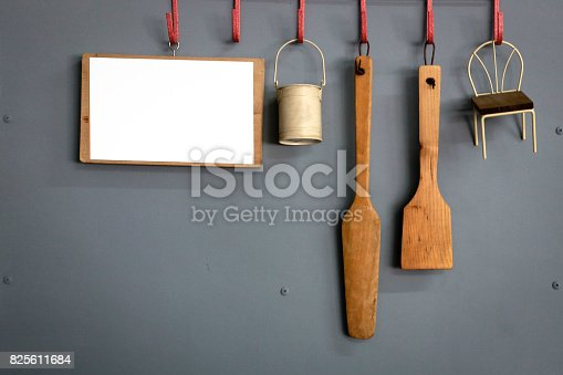 839034546 istock photo Equipment for cooking hanging on a gray wall with white board for writing. 825611684