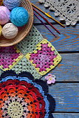 Equipment for knitting and crochet (hook, olorful rainbow cotton yarn, ball of threads, wool, knitted elements, napkin). Granny square. Handmade crocheting crafts. DIY concept. Copy space.