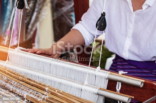 Woman with equipment for weaving silk in Thailand.