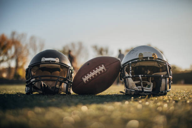 NFL equipment on grass American football helmets and ball on the playing field, no people. ncaa college football stock pictures, royalty-free photos & images