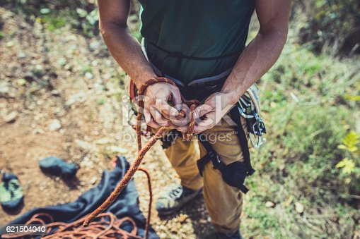 A man is try to tie a knot on his climbing equipment