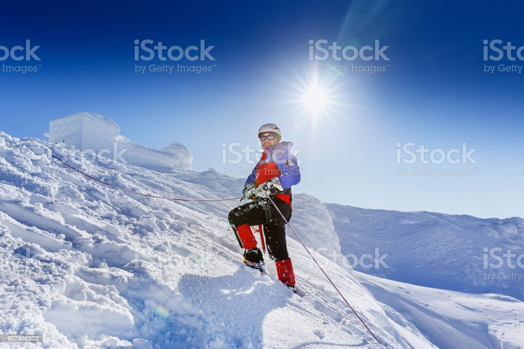 Equipped climber ascent by snowy slope with climbing rope on the top of peak in snowy alpine mountains. Life guard professional man on the work in high mountains. Action in hard conditions scene. Equipped climber ascent by snowy slope with climbing rope on the top of peak in snowy alpine mountains. Life guard professional man on the work in high mountains. Action in hard conditions scene. Activity Stock Photo