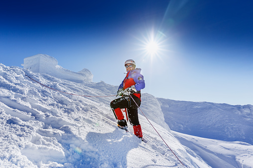 Equipped Climber Ascent By Snowy Slope With Climbing Rope On The Top Of Peak In Snowy Alpine Mountains Life Guard Professional Man On The Work In High Mountains Action In Hard Conditions Scene Stock Photo - Download Image Now