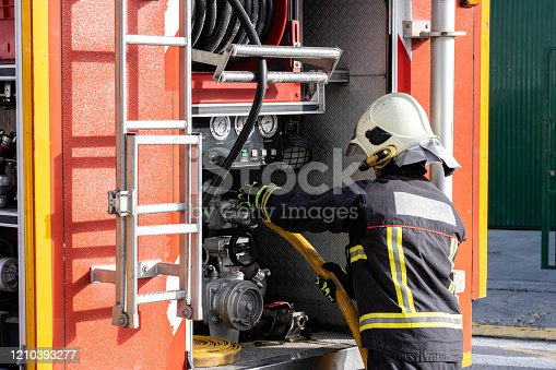istock equipped firefighter handling a water extraction pump, inside a fire truck 1210393277