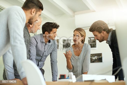 Shot of a group of colleagues talking together over a desk while standing in an office