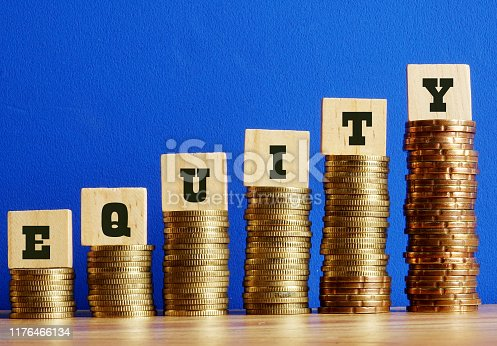 Equity text written on wooden block with stacked coins on blue background