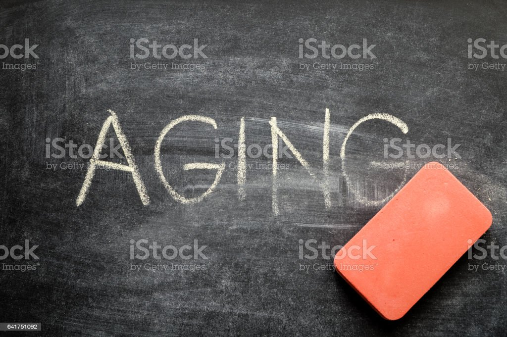 erasing aging, hand written word on blackboard being erased concept stock photo