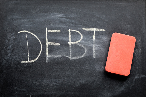 Erasing Debt Hand Written Word On Blackboard Being Erased Concept - Fotografie stock e altre immagini di Affari