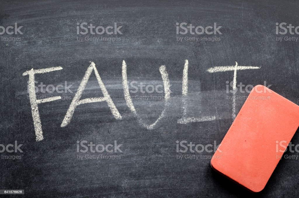 erasing fault, hand written word on blackboard being erased concept stock photo