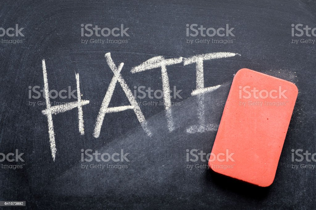 erasing hate, hand written word on blackboard being erased concept stock photo