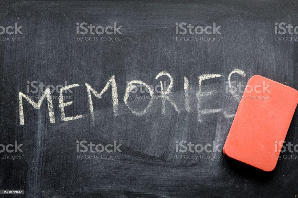 erasing memories, hand written word on blackboard being erased concept stock photo