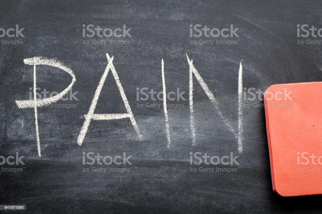 erasing pain, hand written word on blackboard being erased concept stock photo