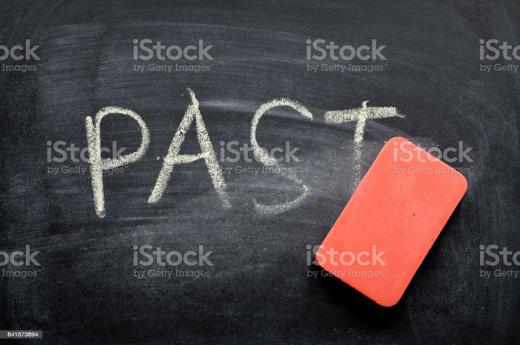 erasing past, hand written word on blackboard being erased concept stock photo