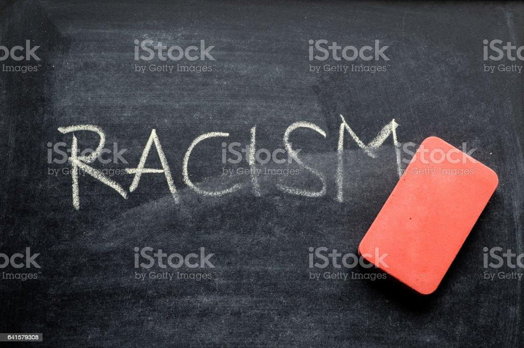 erasing racism, hand written word on blackboard being erased concept stock photo