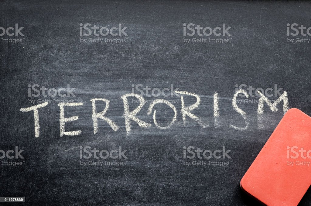 erasing terrorism, hand written word on blackboard being erased concept stock photo