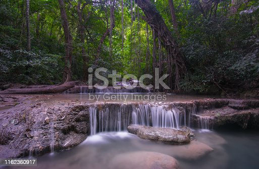 Cascading waterfall surrounded by green forest, long exposure