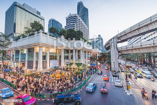 Bangkok, Thailand - January 29, 2017: Pedestrians and traffic in a busy street scene near Siam Square in Bangkok, Thailand. Showing Thao Mahaprom Shrine and the elevated train line.
