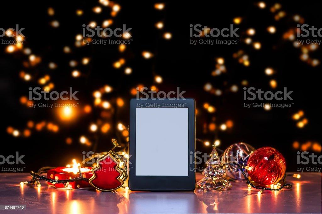 E-reader on flat surface, Christmas theme E-reader on flat surface, christmas them, blurred backgrund, rich colors Christmas Stock Photo