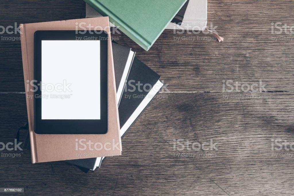 e-Reader auf Stapel Bücher auf rustikalen Schreibtisch aus Holz – Foto