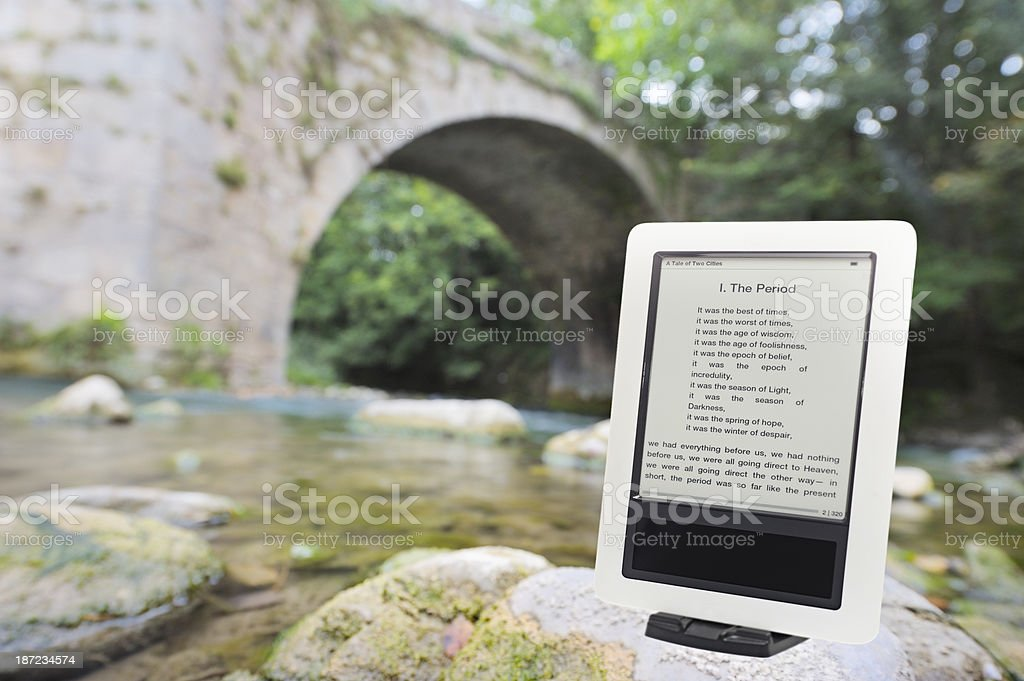 Ereader outdoors by river stock photo