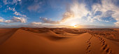 Sunset in the Erg Chebbi desert, Morocco. Is part of the Sahara. The sunset is near, the sun on the horizon. There are footsteps on a dune. The sky is cloudy.