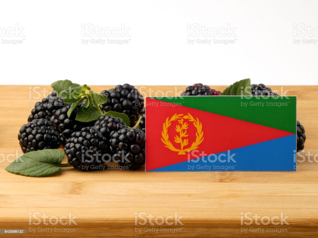 Eritrean flag on a wooden panel with blackberries isolated on a white background stock photo