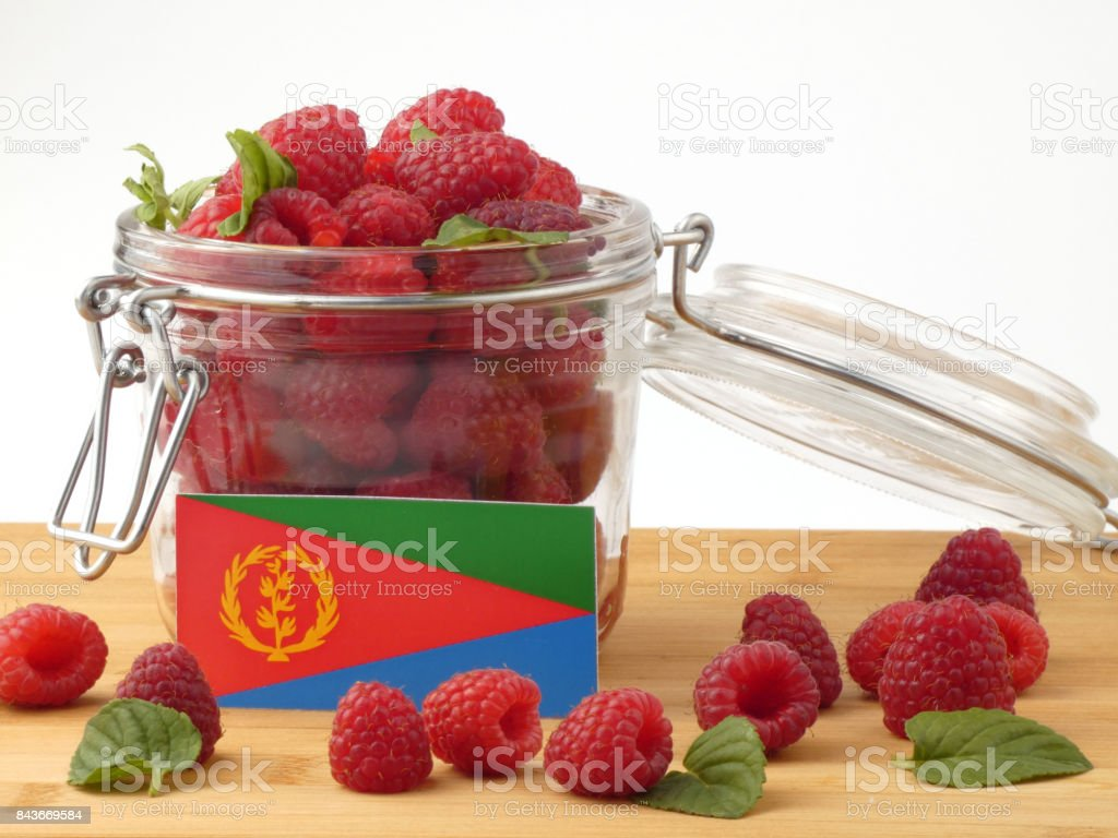 Eritrean flag on a wooden panel with raspberries isolated on a white background stock photo