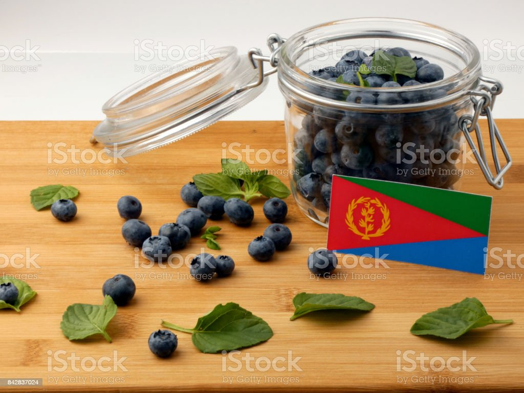 Eritrean flag on a wooden plank with blueberries isolated on white stock photo
