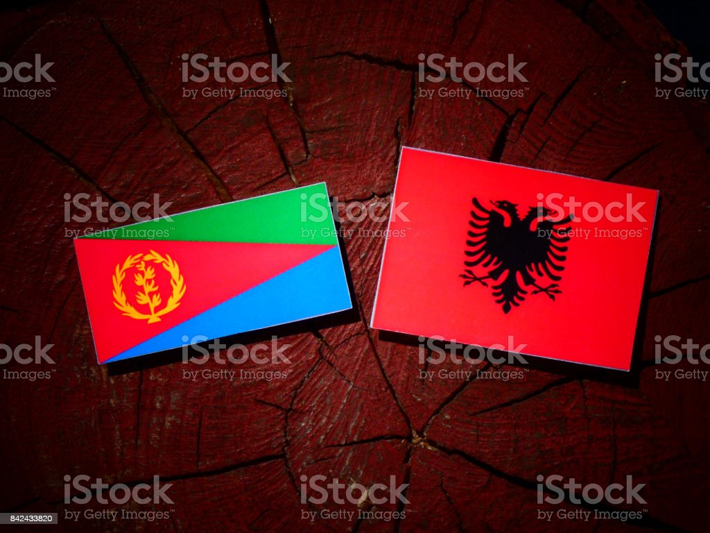 Eritrean flag with Albanian flag on a tree stump isolated stock photo