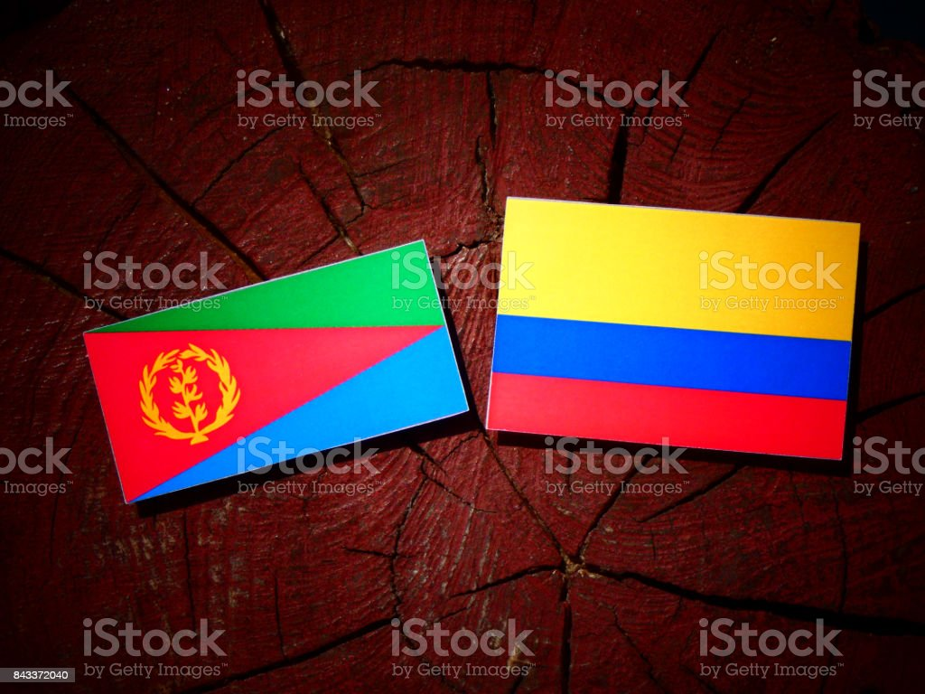 Eritrean flag with Colombian flag on a tree stump isolated stock photo