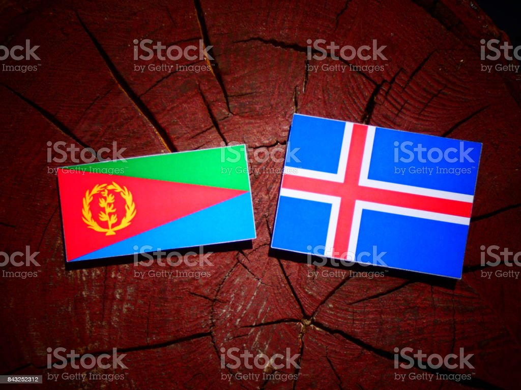 Eritrean flag with Icelandic flag on a tree stump isolated stock photo