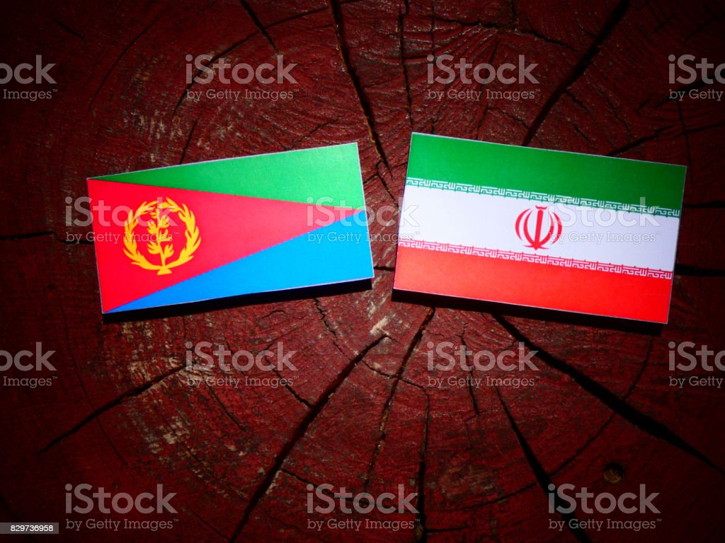 Eritrean flag with Iranian flag on a tree stump isolated stock photo