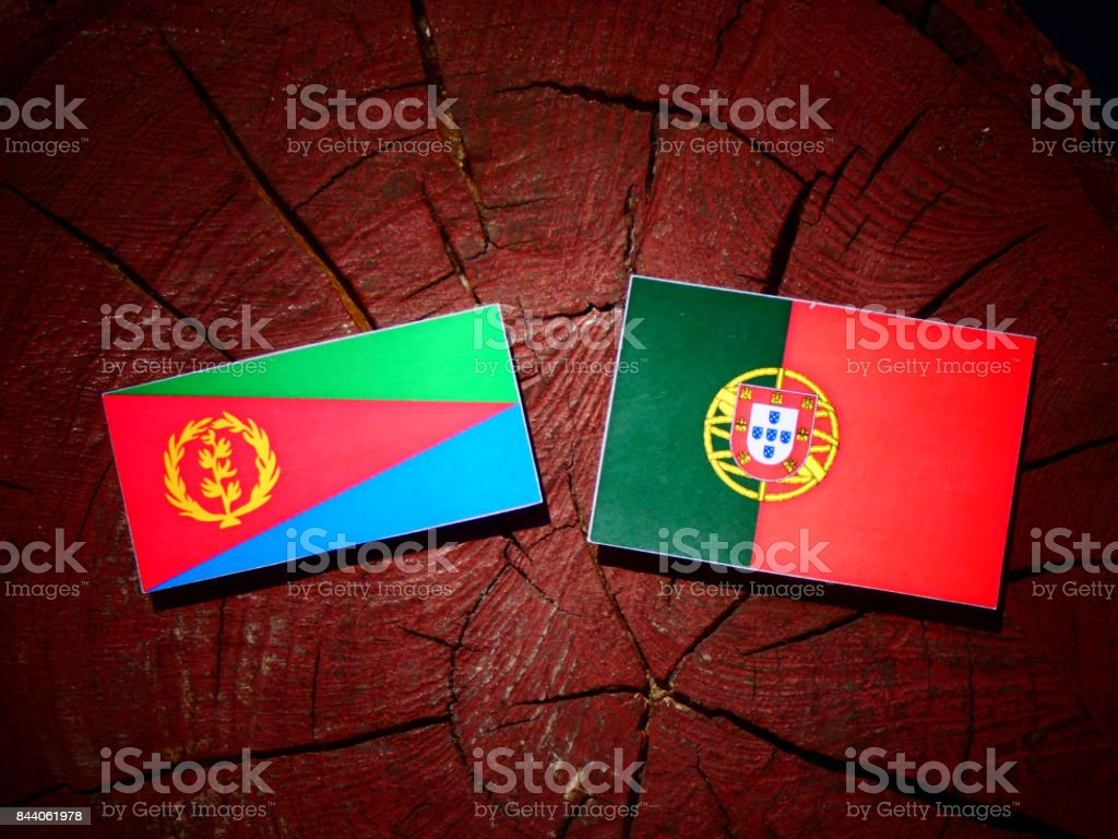 Eritrean flag with Portuguese flag on a tree stump isolated stock photo
