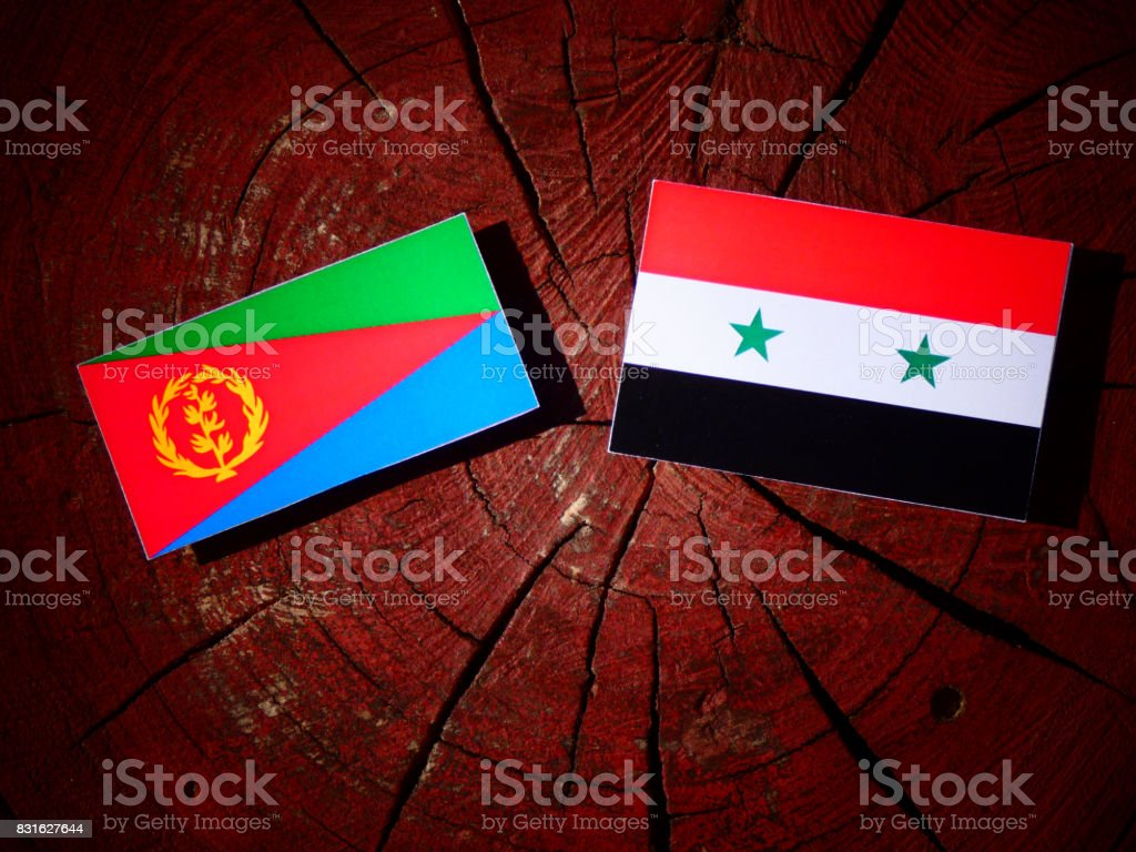 Eritrean flag with Syrian flag on a tree stump isolated stock photo