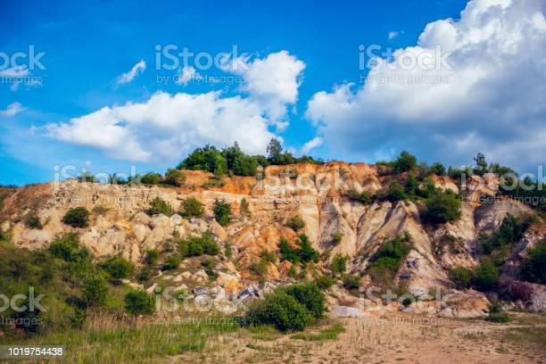 Photo of Eroded limestone rock hill with landslides