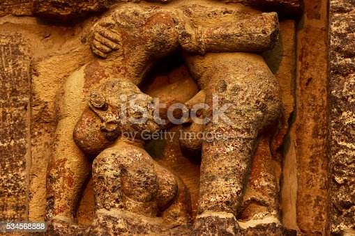 Sculpture of Kama Sutra which depicts woman giving pleasure through mouth and having sex with multiple woman on the wall of Sun Temple in eastern India. In Hindu religion Kama Sutra plays a vital role in day to day life and considered in its purest form. In the picture on right is the sculpture and on left side is  a part  of giant sun wheel.