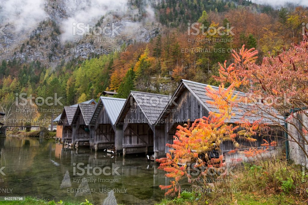 ersonal boathouses in Obertraun town during autumn season with colorful leaf and fog. stock photo