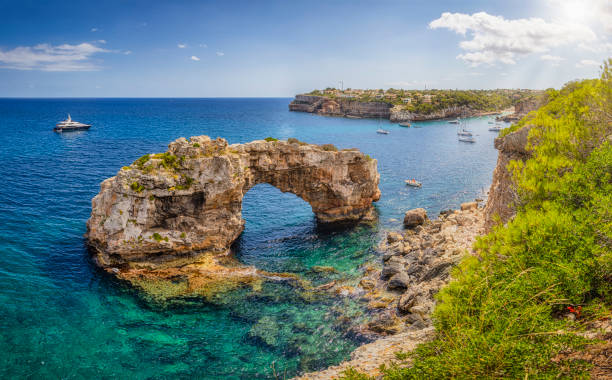 """Es Pontas / Es Pontàs a natural arch near Cala Llombards on the Spanish Balearic island of Majorca - Spain Es Pontàs (""""The big bridge"""") is a natural arch in the southeastern part of the island of Mallorca. The arch is located on the coastline between the Cala Santanyí and Cala Llombards in the municipality of Santanyí. rocky coastline stock pictures, royalty-free photos & images"""