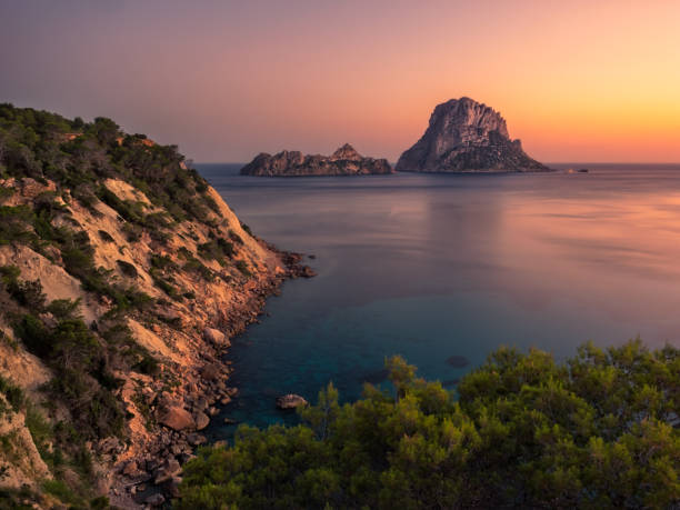 Es Vedra and Es Vedranell at sunset in summer, Ibiza,Spain View of bucolic and beautiful landscape during the sunset, from the cliff, of the Cala D'hort natural park on the island of Ibiza, Spain. In the background the famous islets of Es Vedra, Es Vedranell and the calm and relaxing Mediterranean sea ibiza island stock pictures, royalty-free photos & images