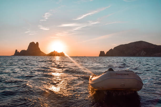 Es Vedra rock island at sunset View from the back of a sailboat of the sunset with the dinghy sailing dinghy stock pictures, royalty-free photos & images