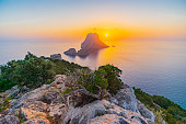 View of the rocky isles of Es Vedrà and Es Vedranell, and Torre des Savinar (a.k.a. Torre del Pirata), off the south-west coast of Ibiza, a golden sunset for one of the most stunning, iconic panoramas of the island. Developed from RAW.