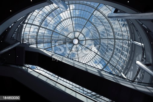 istock Escalators, Glass Roof and Skyscraper against blue sky 184853030