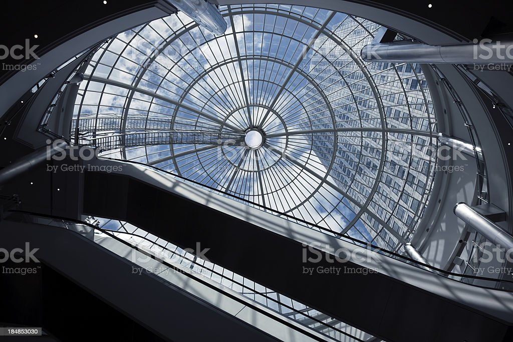 Escalators, Glass Roof and Skyscraper against blue sky stock photo